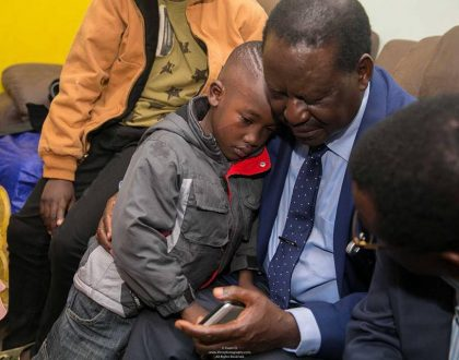 Photos of the day: Chris Msando's youngest son seeks solace in Raila Odinga