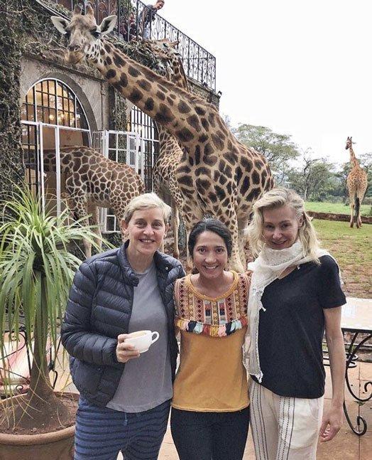 Ellen DeGeneres, her wifePortia de Rossi and a friend pose for a photo at theGiraffe Manor