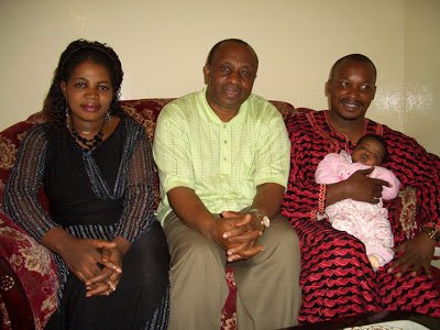 Prophet Elisha Muliri carries his daughter Wonder Glory when she was still months old. Seated on the left is Angela Chibalonza.
