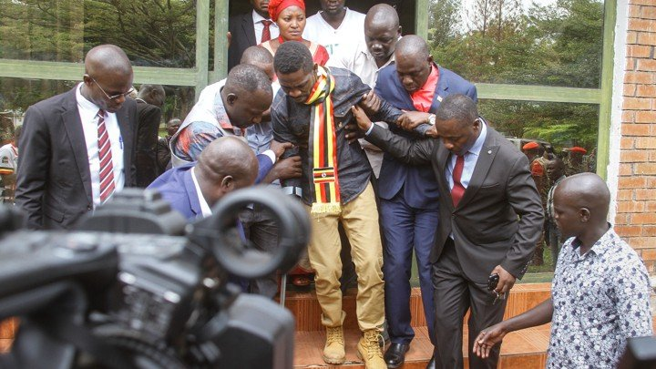 A frail Bobi Wine being supported as he walks out of the courthouse