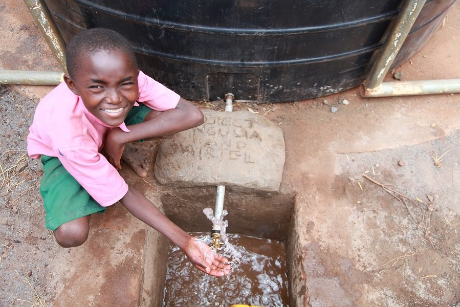 A pupil at Matangini Primary School enjoys the free flowing water from the water tank donated to the school by Airtel.