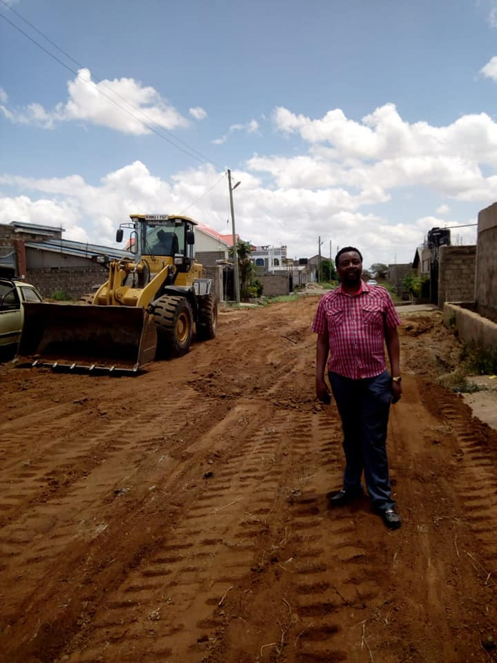Pastor Godfrey Migwi stands next to a heavy construction vehicle that was fixing a public road he paid for with his own money