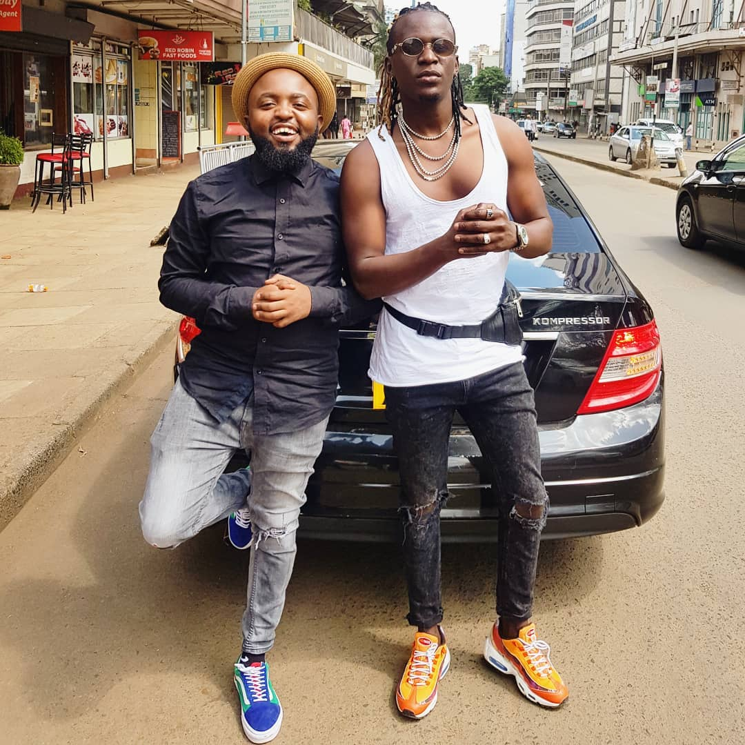 Willy Paul posses next to his Mercedes Benz