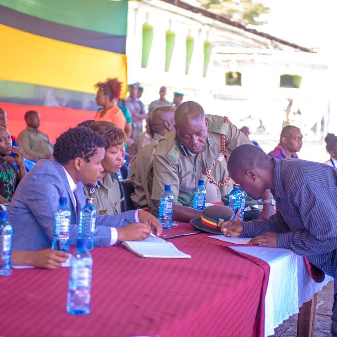 Barack Odero Oluoch (signing papers)  with Chipukeezy and prison wardens