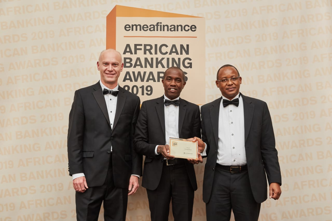 (L-R) The Publisher and CEO EMEA Finance Christopher Moore grants the Best Bank in Kenya 2019 Award to Co-op Bank Economist Anthony Muli and Head of Investor Relations and Strategy James Kaburu at the EMEA Awards gala