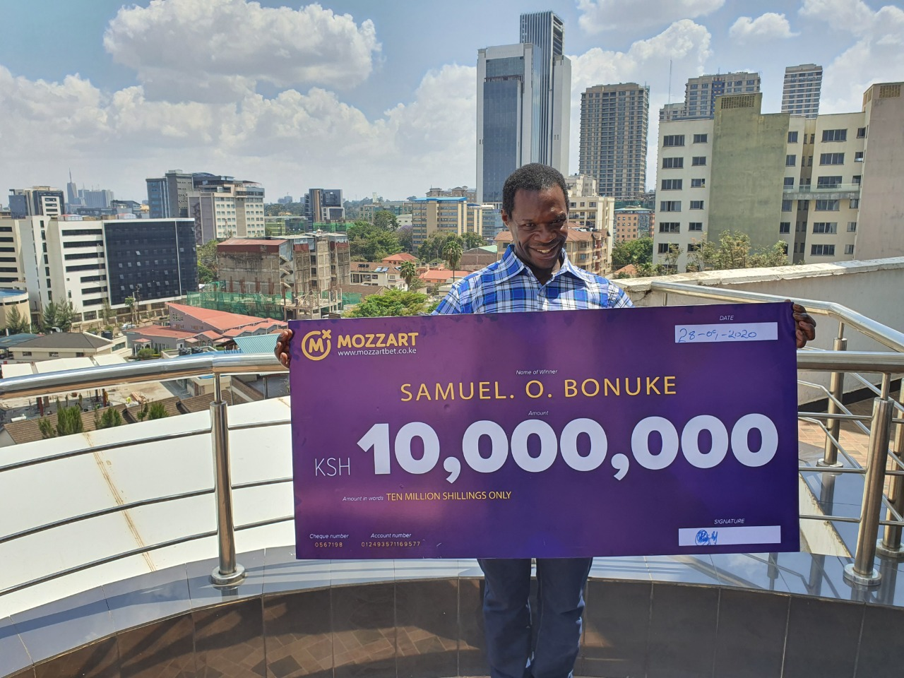Mr. Samuel Bonuke poses with his ksh. 10m dummy cheque in Nairobi